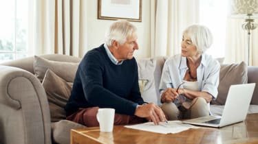 picture of elderly couple working on finances in their living room