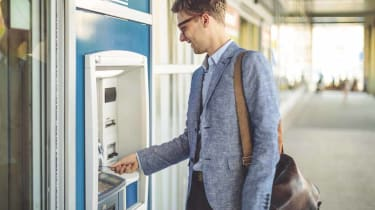 Young man is withdrawing cash from an atm machine