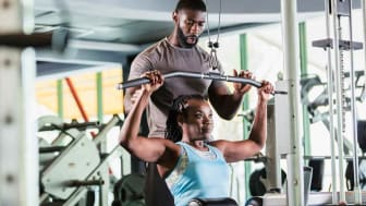 Woman at gym with trainer helping her lift weights