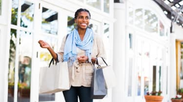 Beautiful Girl in her 20s loves shopping. Young woman is of Black descent. African American woman is walking in a mall and holding three shopping bags. Her hair is in braids. Woman is dresses