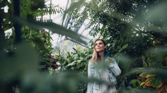 Female gardener in plant nursery. Young caucasian woman working in a garden center.