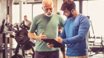 A senior man with a personal trainer in a gym