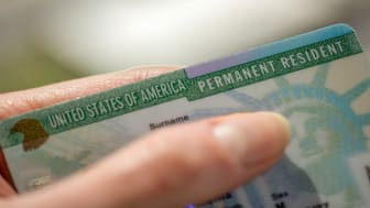 picture of a person holding a green card