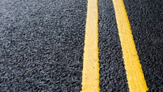 Close-up on yellow lines painted on fresh black tarmac.