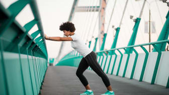An athletic woman warming up before she starts to run on city bridge