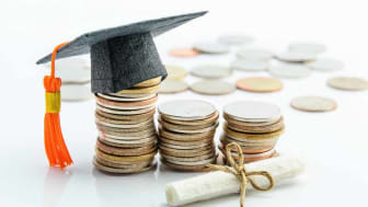 Money cost saving or money reserve for goal and success in school, higher level education concept : US dollar coins / cash, a black graduation cap or hat, a certificate / diploma on white bac