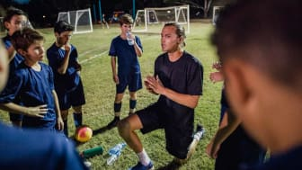 A coach on a soccer field talking to his young players in uniform