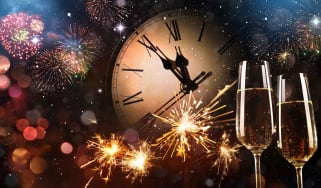 Concept art of New Year's Eve with a clock about to strike 12, fireworks and champagne