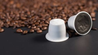 Two K-cup coffee pods next to whole coffee beans