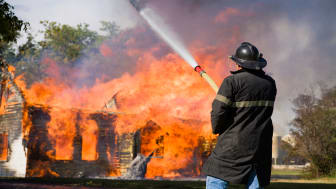 picture of firefighter spraying water on burning house