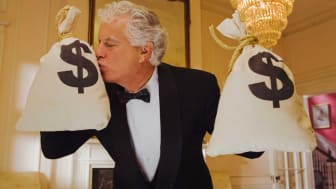 picture of man dressed in a tuxedo holding two large bags of money and kissing one of the bags