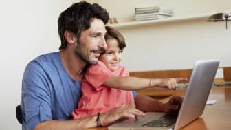 Happy father and son using laptop together at table in house