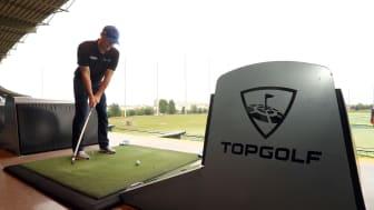 A man tees off at a TopGolf teebox