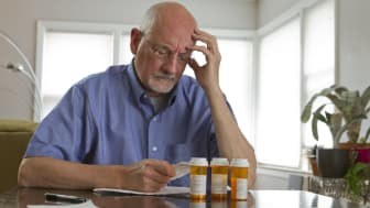 Older man with prescription bottles, horizontal