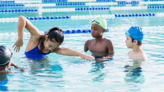 A teen girl gives swimming lessons at a pool.