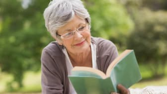 Relaxed senior woman reading a book at the park
