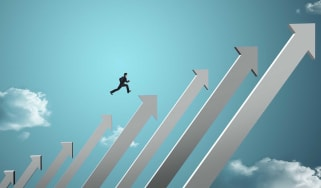 A businessman jumping on increasingly large arrows that are pointed upward