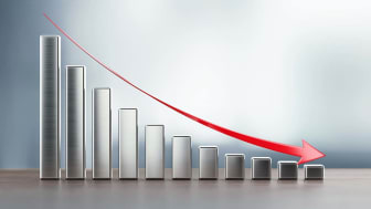 Metallic financial chart and a red arrow on wood surface are showing a drastic decrease. Horizontal composition with selective focus and copy space.