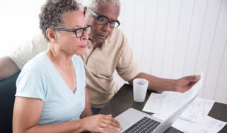 Senior couple sitting at table, using laptop, looking at bills
