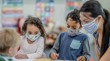 Kids at daycare with daycare associate in masks