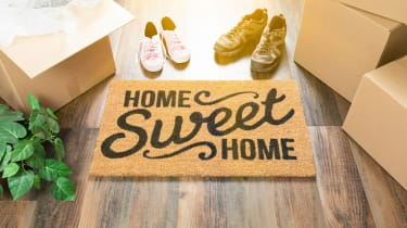A welcome mat, surrounded by boxes and shoes, says home sweet home.