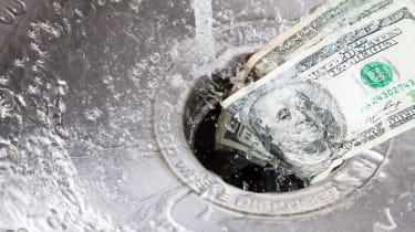 picture of money going down a kitchen sink drain