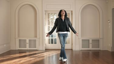 A young woman celebrates inside her new home.