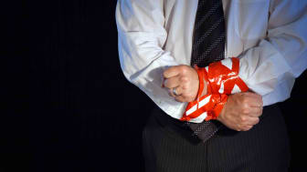 A businessman whose hands are bound by red tape