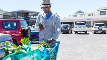 Retiree pushing full shopping cart while looking at smart phone