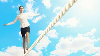 Businesswoman balancing on rope