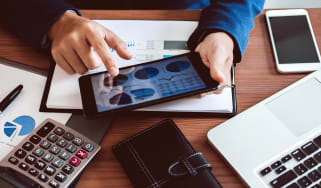 Businessman hands using text information on digital tablet to analyze financial statistical chart data and calculate cost of investment project. (Businessman hands using text information on d