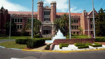 A fountain on a roundabout with a Welcome to The Florida State University sign in front of a building with towers at the entrance, Tallahassee, Florida