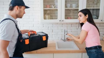 Woman explaining to handyman issue with faucet