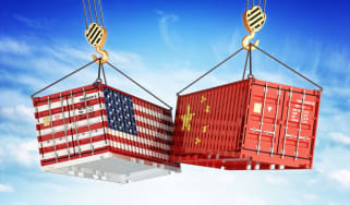 Freight transportation concept, cargo containers with USA and China flags hoisted by crane hooks on blue cloudy sky background