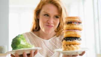 A woman chooses between an apple and a huge hamburger.