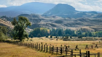 A fenced farm and the mountains of Montana