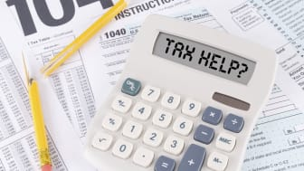 """A calculator reads """"tax help"""" sitting on tax forms"""