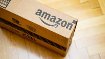 Amazon logotype printed on cardboard box side seen from above on a wooden parquet floor