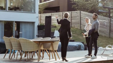 Real estate agent showing new property to couple outdoors