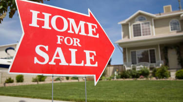 """An arrow shaped red """"Home For Sale"""" sign in front of a suburban 2-story home.The green grass and blue sky is visible in the background."""