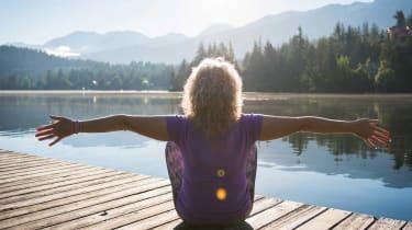 Woman doing yoga on a dock at a lake