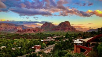 The painted sky of Sedona Arizona in the fall as the sun drops below the desert horizon makes for a stunning backdrop for contemporary homes perched on hills of green.