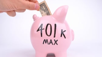 "picture of person putting money is a piggy bank with ""401k Max"" written on it"