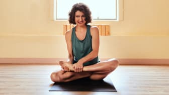 A woman looks uncomfortable as she tries to get into a yoga pose.