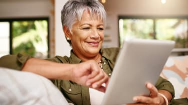 Shot of a happy older woman relaxing on the sofa with her digital tablet at home