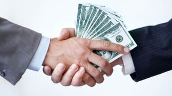picture of one man giving another man a handful of money