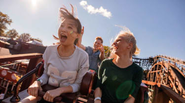 People smile and yell while on a roller coaster
