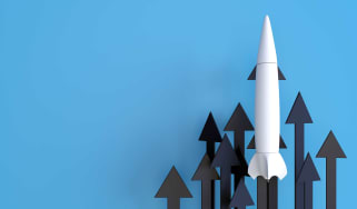 A white rocket moving higher against a background of arrows also moving higher, all against a blue background