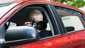 picture of private investigator taking a picture from his car