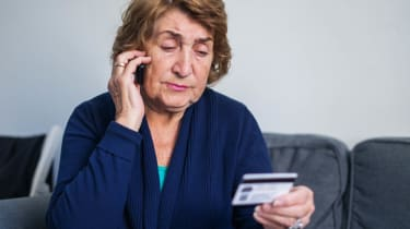 An older woman reads the numbers off a gift card to a caller.